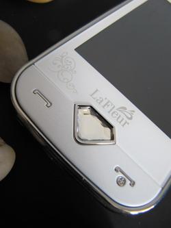 Жемчужно-белая   отделка, рельефная задняя крышка, центральная кнопка в виде граненого   бриллианта на лицевой панели.